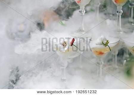 steaming pyramid of glasses for champagne at outdoor garden in wedding ceremony