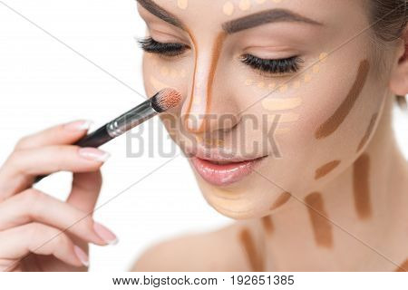 Cheerful lady is using cosmetic brush in order to shade various kinds of concealer. Portrait. Isolated