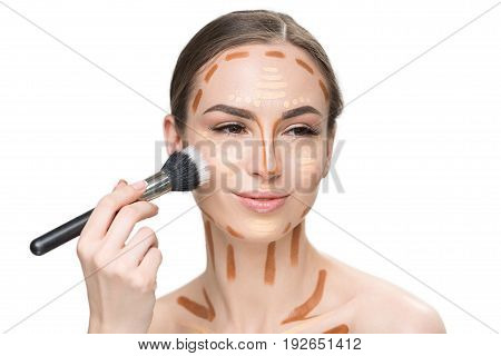 Happy woman is working with professional cosmetic brush in order to shade concealers and looking aside with smile. Portrait. Isolated