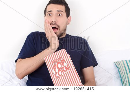 Young man eating popcorn and watching movies relaxed on bed. Indoors.