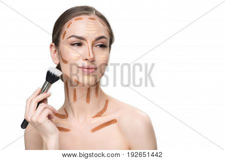 Happy smiling girl is holding special cosmetic brush and going to shade various correctors on her face. Portrait. Isolated