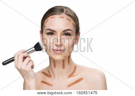 Confident young lady is using professional brush in order to shade concealers on her face and looking at camera with light smile. Portrait. Isolated and copy space