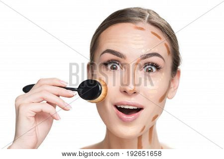 Surprised young woman is shading concealer on her cheek and looking at camera with deep wonder. Portrait. Isolated