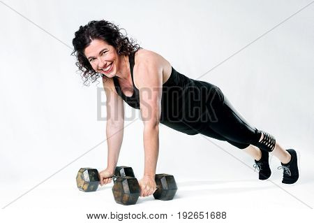 A happy muscular woman with curly black hair does a plank on a white background as she smiles for the camera. She is on dumbbells with straight arms.