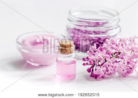 spa cosmetic set with lilac flowers on white desk background