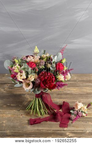 Bridal bouquet and boutonniere. Red and peach color flowers. stand on vintage wooden table and grey wall