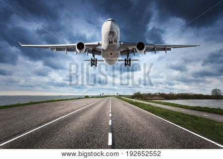 Airplane and road. Landscape with big white passenger airplane is flying in the cloudy sky over the asphalt road. Journey. Passenger airliner is landing on the runway. Commercial plane and highway