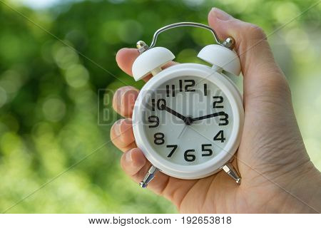 woman hand holding a white alarm clock as business or time countdown concept with green bokeh in summer sun shine.
