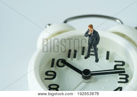 miniature thinking businessman figure standing on white alarm clock as business or time countdown concept.