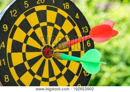 selective focus on a green and red darts pin in the center of dartboard with green bokeh background as Business goals or targets concept.