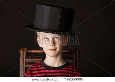 Charismatic Little Boy Wearing An Out Size Top Hat