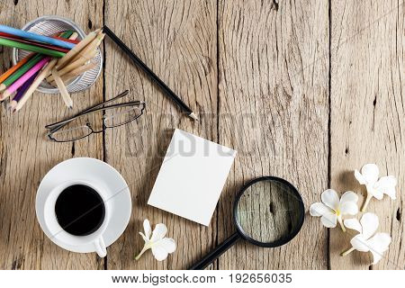 business objects of keyboardmousewhite coffee cupwhite paperpencilsglassesmagnifying glass and frangipani flowers on old wooden table background