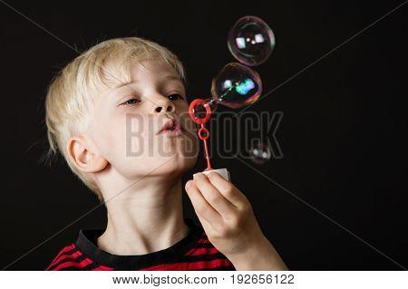 Attractive Little Blond Boy Blowing Bubbles