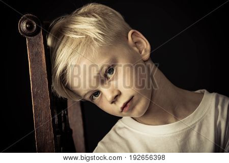 Thoughtful Little Blond Boy Sitting On A Chair