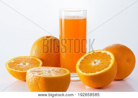 A glass of orange juice creating a splash among oranges