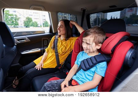 Mid shot of a mother and her son in the automobile; sitting on back seats, buckled up, smiling people