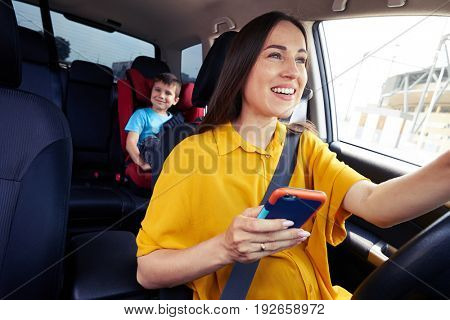Close-up shot of a mother driving a car, buckled the seat belt, holding phone. Laughing boy on back seat