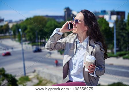 Mid shot of beautiful madam talking on phone while holding cup of coffee on top of building