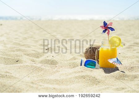 Glass of orange juice, coconut, sunglasses, umbrella and spinner with stars and stripes - 4th of July on the beach.