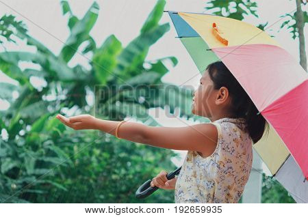 Children in the rain Have fun playing in park and have umbrellas