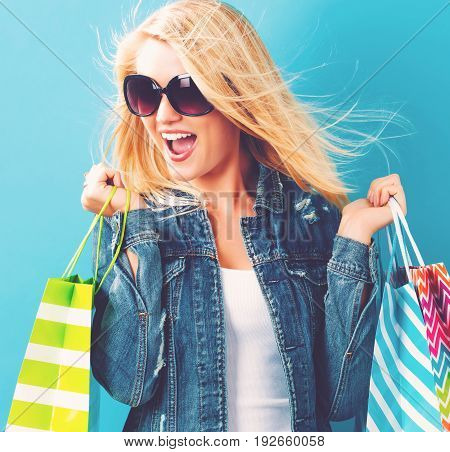 Happy young woman holding shopping bags on a blue background