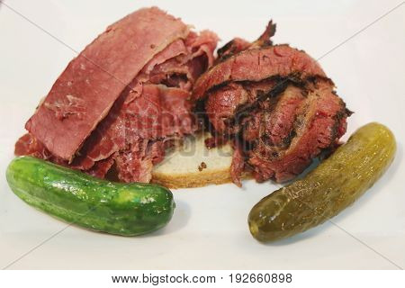Famous Corned Beef and Pastrami on rye sandwich served with pickles in New York Deli
