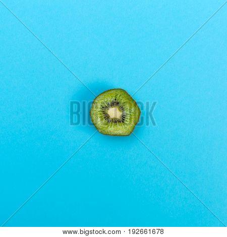 Slice of kiwi on a bright blue background