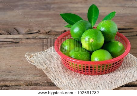 A Lime Lemon In Red Bucket On Rustic Wooden Background. Copy Space For Graphic Designer