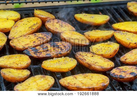 Grilling delicious potatoes on barbecue. Slice potato are prepared on the grill on sunny day. Close up. Culinary concept.