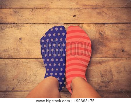 Selfie feet wearing blue sock with white star shape and red one wth white striped on wooden floor background vintage filter effect. American flag and 4th of July concept.