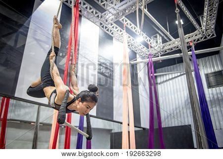 Young Asian gymnast woman doing gymnastics on rope in aerial fitness gym