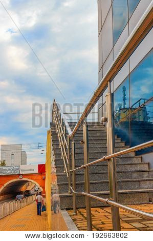 The road and the sidewalk leaders in a tunnel and on the right a wall of the modern house with the stone ladder and a metal handrail going as if to the sky. Day sky cloudy.