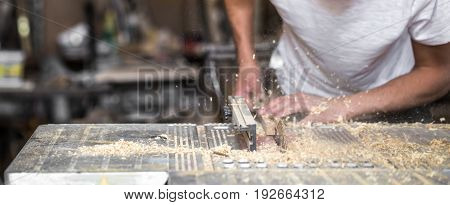 a man working with wood product on the machine, closeup