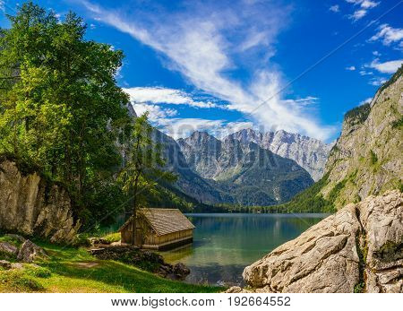 Wooden cabin on idyllic coast against alpine mountains and wonderful cloudscape. Obersee lake Berchtesgadener Land Bavaria Germany