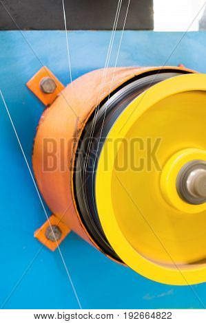 A rotating wheel rewinds a thin silver wire. Automatic winding machine.