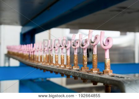 Homemade wire holders, in the form of curly loops set in a row on a metal bar.