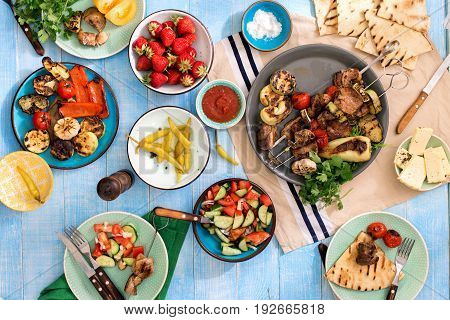 Different food cooked on a grill on a blue wooden table top view. Dinner table with shish kebab grilled vegetables salad snacks and strawberries