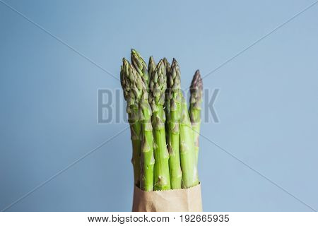 Bundle of green asparagus on blue background. Concept of vegans, vegetarians and healthy food.