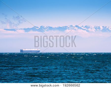 Large cargo ship in the Pacific Ocean against the mountain background