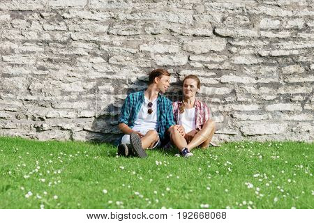 Young and happy couple chilling in park. Love, relationship, romance concept.