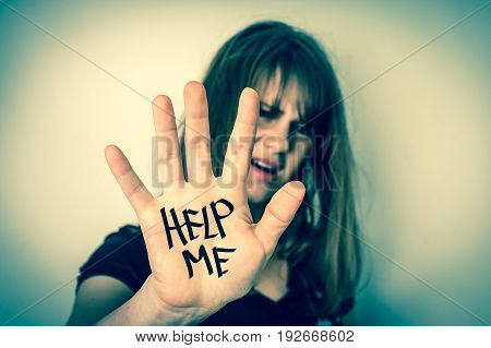 Woman covers her face with hand and showing message help me - violence concept - retro style