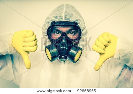 Man In Coveralls With Gas Mask Is Showing Negative Gesture