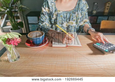 business women is calculating the expense on the wooden table with hot mocha coffee and red flower