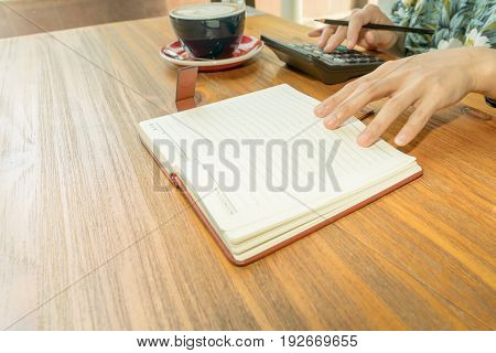 business women is calculating the expense on the wooden table with hot mocha coffee