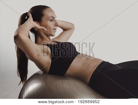 Shot of a beautiful young woman making crunchs on a swiss ball