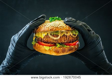 Tasty burger sandwich in hands weared black gloves background