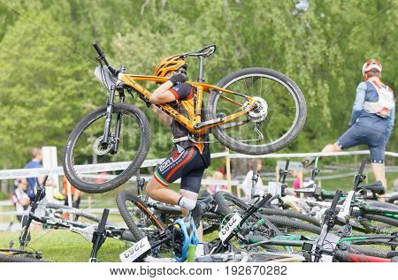 STOCKHOLM SWEDEN - JUNE 11 2017: Man carrying his mountainbikes before the start in the race at Lida Loop Mountainbike Race. June 11 2017 in Stockholm Sweden