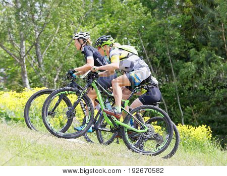 STOCKHOLM SWEDEN - JUNE 11 2017: Three female mountain bike cyclists cycling uphill at Lida Loop Mountain bike Race. June 11 2017 in Stockholm Sweden