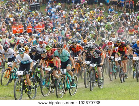 STOCKHOLM SWEDEN - JUNE 11 2017: Large group of fighting mountainbike cyclists i cycling uphill at Lida Loop Mountainbike Race. June 11 2017 in Stockholm Sweden