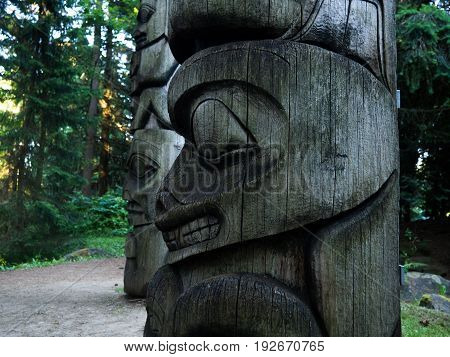 Smiling totem pole statue in forest - Canada